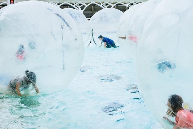 Gruppe kinder, die spaß innerhalb der ballone wasser-gehenden kugel haben