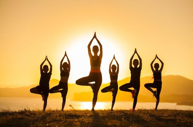 Gruppe kinder nehmen an yoga mit einem trainer auf dem ozean teil.