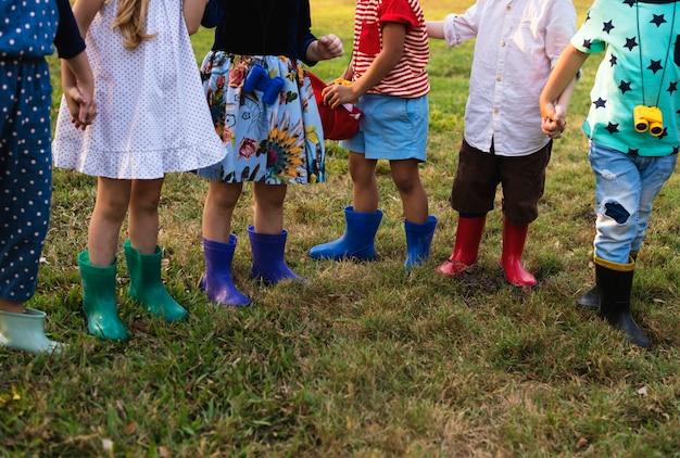 Gruppe kinder schulen feldreisen, die draußen botanischen park lernen