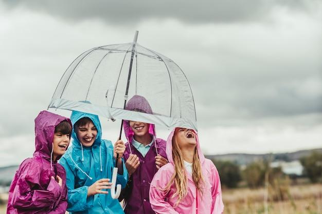 Gruppe kinderfreunde spielen und lächeln in den regenflüchtlingen innerhalb eines regenschirmes an einem regnerischen tag in der landschaft