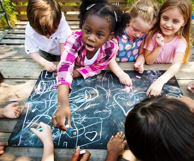 Gruppe kindergarten scherzt die freunde, die draußen kunstunterricht zeichnen