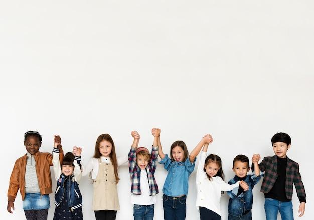 Gruppe kinderhändchenhaltengesichtsausdruck-glück, das auf weißem blackground lächelt