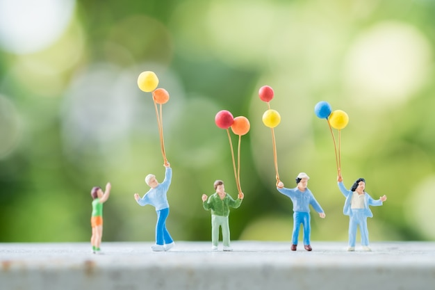 Gruppe kinderminiaturleute stellt mit buntem ballon mit grüner natur dar.
