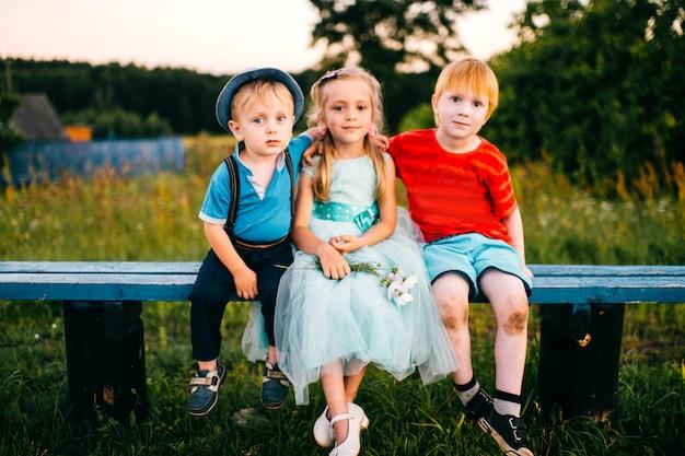 Gruppe kleine emotionale kinder, die auf der bank im freien in der landschaft sitzen. mädchen im kleid zwischen zwei jungs. schwierige beziehungen. eifersucht der jugend. lustiges liebendes dreieck. freude, trauer, schmerz und beleidigung