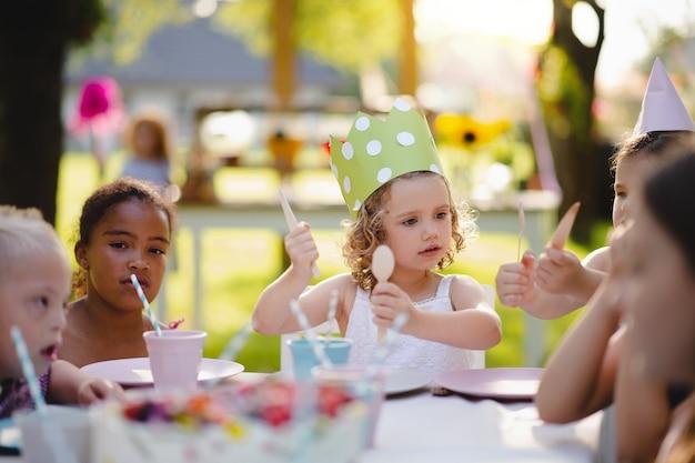Gruppe kleiner kinder, die draußen auf der gartenparty am tisch sitzen und essen.