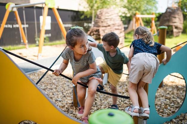Gruppe kleiner kindergartenkinder, die draußen auf spielplatz spielen.