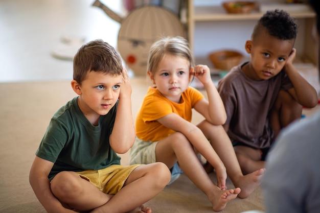 Gruppe kleiner kindergartenkinder, die drinnen im klassenzimmer auf dem boden sitzen und dem lehrer zuhören.