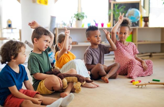 Gruppe kleiner kindergartenkinder, die drinnen im klassenzimmer auf dem boden sitzen und die hände heben.