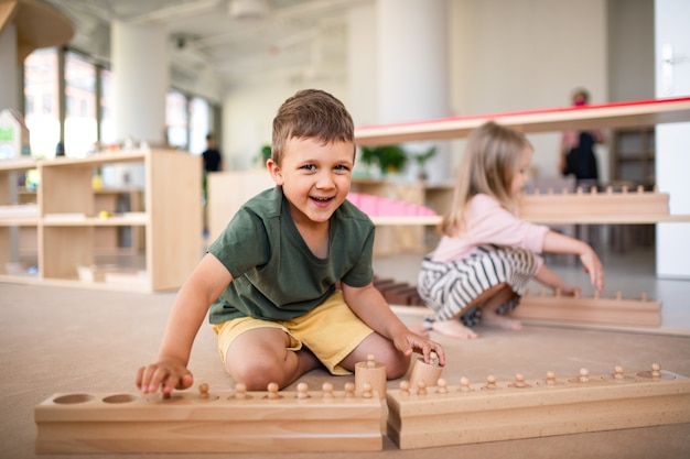 Gruppe kleiner kindergartenkinder, die drinnen im klassenzimmer spielen, montessori-lernen.