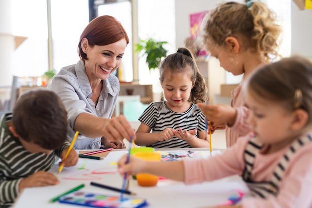 Gruppe kleiner kindergartenkinder mit lehrer drinnen im klassenzimmer, malerei.