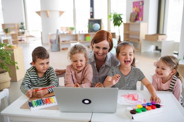 Gruppe kleiner kindergartenkinder mit lehrer drinnen im klassenzimmer, mit laptop.