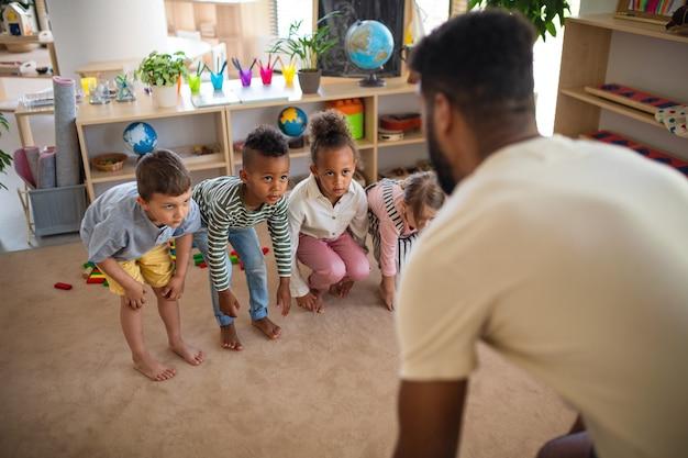 Gruppe kleiner kindergartenkinder mit mannlehrer drinnen im klassenzimmer, das übungen macht