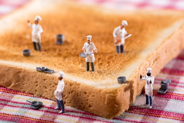 Gruppe köche oder chefs auf einer scheibe des weißen toasts