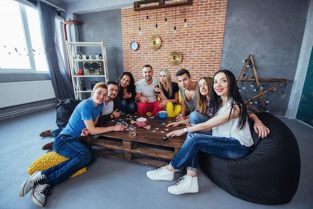 Gruppe kreative freunde, die am holztisch sitzen. leute, die spaß beim spielen des brettspiels haben