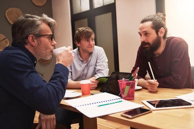 Gruppe kreativer menschen, die das ergebnis der arbeit analysieren