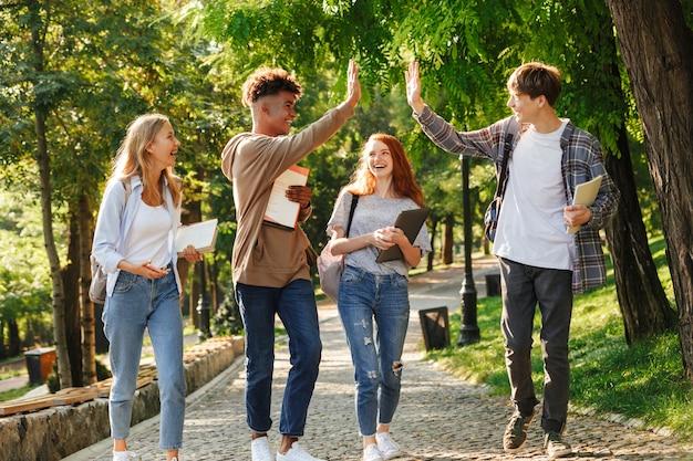 Gruppe lachender studenten, die auf dem campus spazieren gehen