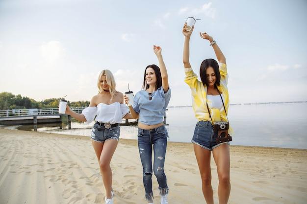 Gruppe lächelnde junge frauen, die auf strand tanzen.