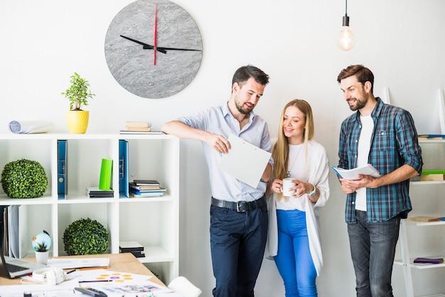 Gruppe lächelnde junge wirtschaftler, die dokument im büro betrachten