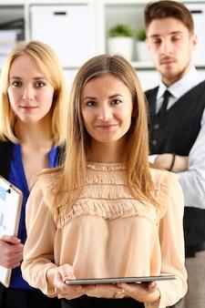 Gruppe lächelnde leute stehen im büro, das in camera schaut