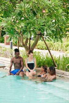 Gruppe lächelnder freunde, die im schwimmbad des spa-hotels entspannen und pläne für den tag besprechen