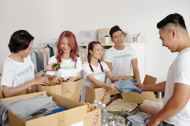 Gruppe lächelnder junger freiwilliger, die kleidung und lebensmittel für bedürftige in kartons verpackt