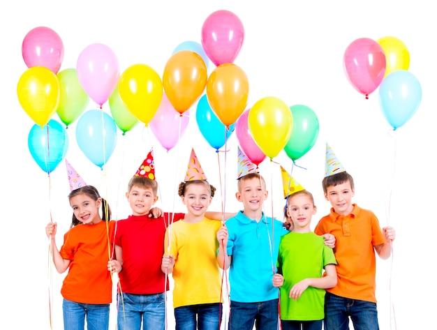 Gruppe lächelnder kinder in den farbigen t-shirts und in den parteihüten mit luftballons auf einem weißen hintergrund