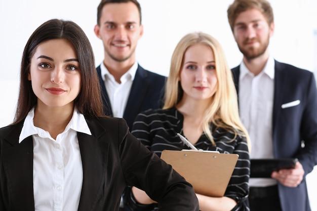 Gruppe lächelnder menschen steht im büro und schaut in die kamera
