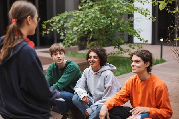 Gruppe lächelnder studenten, die sitzen und glücklich zeit zusammen im hof der universität verbringen