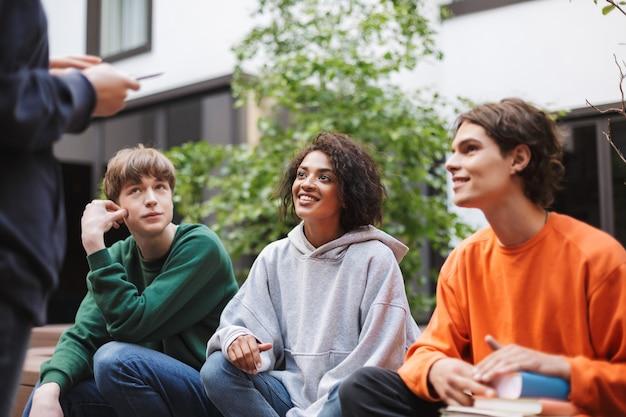 Gruppe lächelnder studenten, die sitzen und träumerisch beiseite schauen, während sie zeit zusammen im hof der universität verbringen