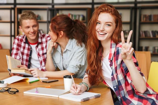 Gruppe lächelnder teenager, die hausaufgaben machen