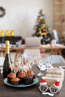 Gruppe leckerer hausgemachter muffins mit kleinen weihnachtskarten auf dem teller, umgeben von einer flasche champagner, weihnachtsmannbrillen, flöten und geschenkboxen