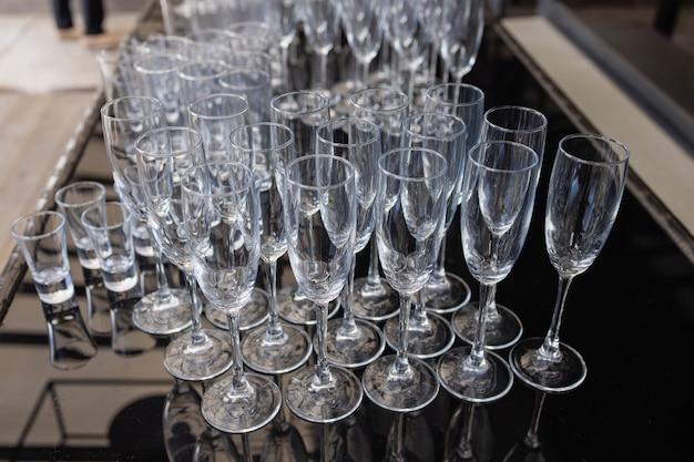 Gruppe leerer und transparenter champagnergläser in einem restaurant. saubere gläser auf einem tisch, der vom barkeeper für champagner vorbereitet wurde.