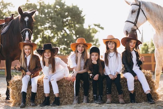 Gruppe mädchen, die auf heu mit pferden sitzen