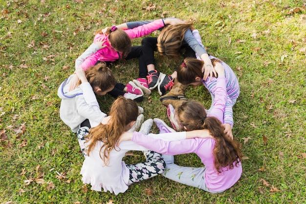 Gruppe mädchen, die zusammen in der unordnung auf grünem gras sitzen