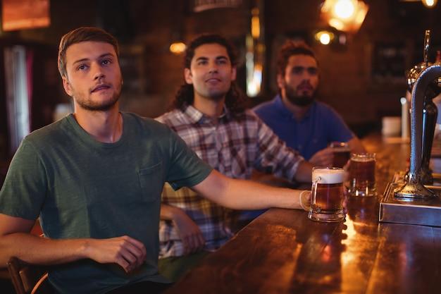 Gruppe männlicher freunde, die fußballspiel beobachten