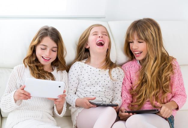 Gruppe mit drei kindergeschwisterfreunden, die zusammen mit tablet-pc spielt