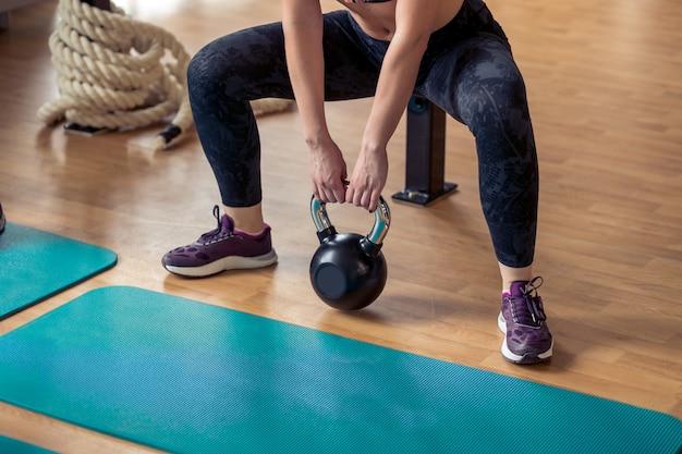 Gruppe mit funktionellem fitnesstraining mit kettlebell im sport-fitnessstudio