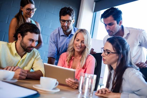 Gruppe mitarbeiter, die einen tablet-computer aufpassen