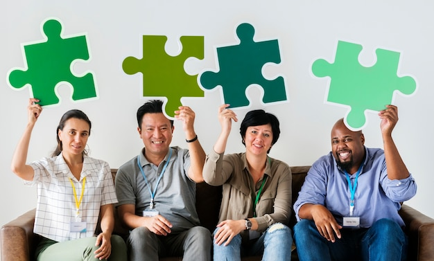 Gruppe mitarbeiter, die puzzlespielikonen halten