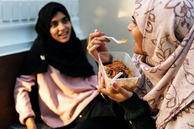 Gruppe moslemische mädchen, die zusammen zu mittag essen
