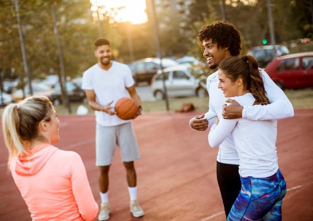 Gruppe multiethnische leute, die basketball auf gericht spielen