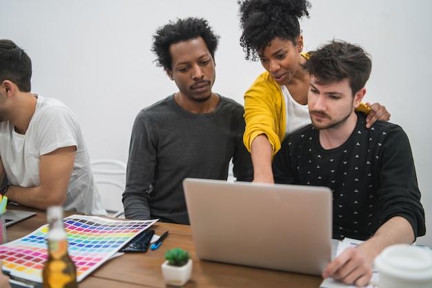 Gruppe multiethnischer kreativer geschäftsleute, die an einem projekt arbeiten. geschäftsfrau, die auf den bildschirm zeigt und ihren kollegen etwas zeigt. unternehmenskonzept.