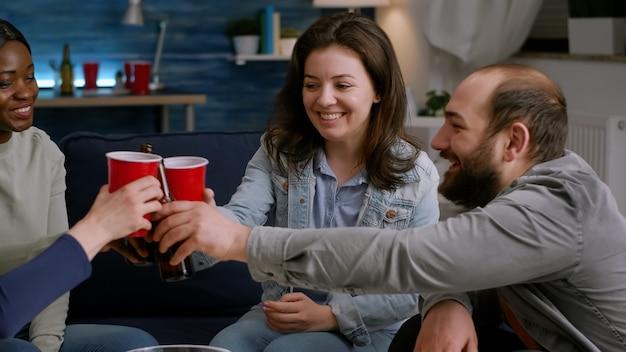 Gruppe multikultureller glücklicher freunde, die sich während der kostenlosen wochenendparty amüsieren und bier trinken und snacks essen ...