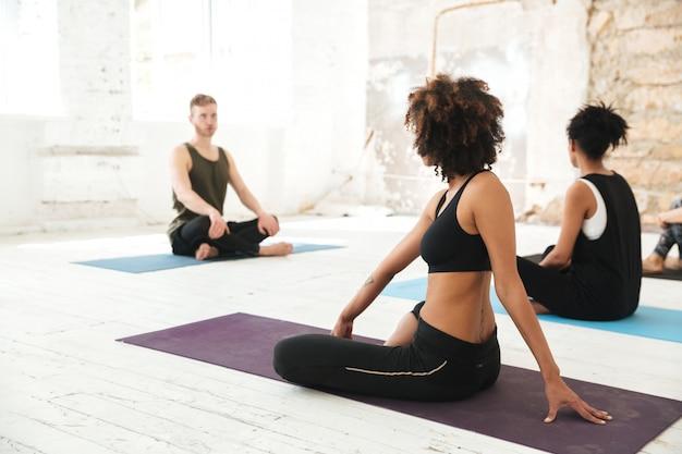 Gruppe multikultureller junger menschen, die yoga praktizieren