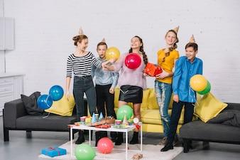 Gruppe nette Freunde, die zu Hause die Geburtstagsfeier feiern