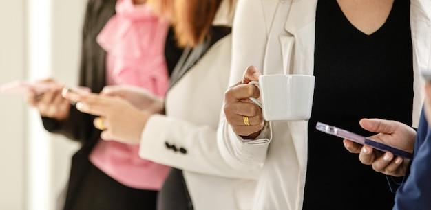 Gruppe nicht erkennbarer geschäftsfrauen, die zur bruchzeit im amt zusammenstehen. die teamarbeit der weiblichen mitarbeiter entspannt und einfach, während sie das smartphone benutzt und kaffee trinkt.