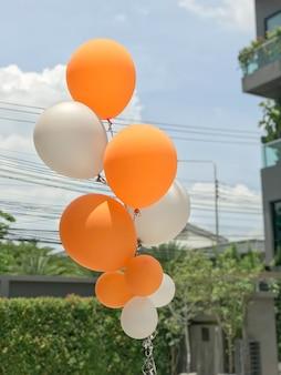 Gruppe orange und weiße ballonballone für parteidekoration.