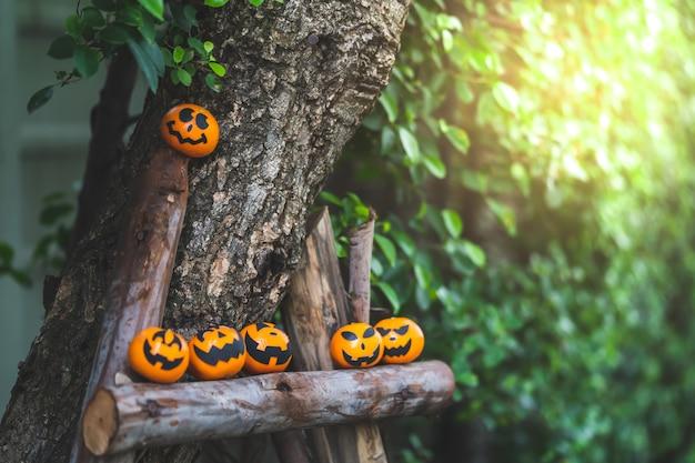 Gruppe orangengesichtsmalerei mit furchtsamem am halloween-parteitag am gartenplatz.