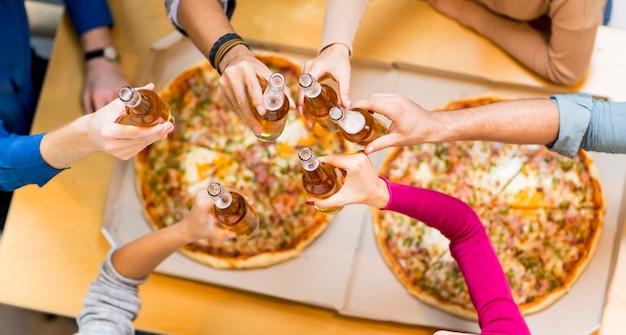 Gruppe oung leute, die pizza essen und apfelwein in der modernen innenansicht von oben trinken