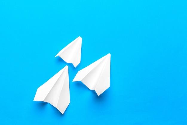 Gruppe papierflugzeuge auf blauem hintergrund.